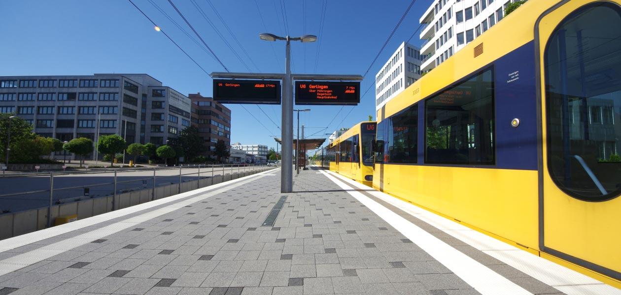 Straßenbahnhaltestelle mit weißen Leitstreifen.