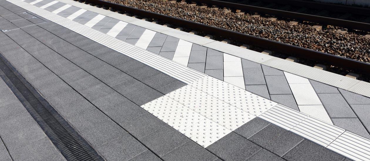 Bahnhof-Haltestelle mit weißen Leitstreifen und Abzweigungsfeld.