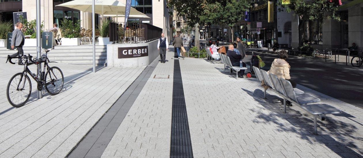 Schwarzer Leitstreifen aus Rippenplatten vor einer Einkaufspassage in Stuttgart.